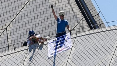 A protester raises his arm after being stopped by police from putting a protest sign on top of the Sydney Opera House