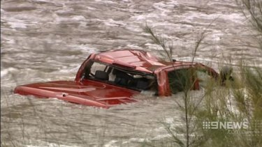 A red car in the swollen Cotter River where a 37-year-old man's body was found.
