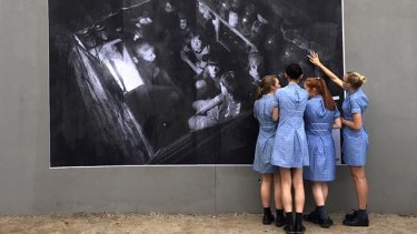 At McKinnon Secondary College, in Melbourne, the #Dysturb collective spoke with students about the power of photojournalism and the changing media landscape. Pictured is an image by Andy Rocchelli that the students helped to paste in the school. The caption reads: Ukraine, Sloviansk, Cherevkovka District. A family hides from the bombardment in the cellar.