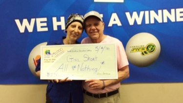 Gina Short brandishes her lottery cheque with her husband Len.