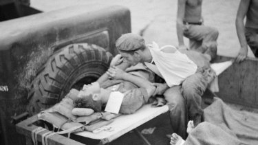 A soldier comforts his shell-shocked friend while they wait to be evacuated from Papua New Guinea during World War II.