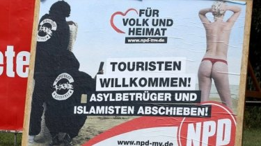 "A poster of Germany's far-right NPD in which 'rapefugees' take photos of a beachgoer: ""Tourists welcome - asylum cheaters and Islamists out!"""