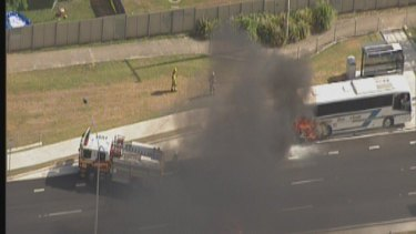Firefighters use high-pressure hoses to control a bus fire on Anzac Avenue at Rothwell.