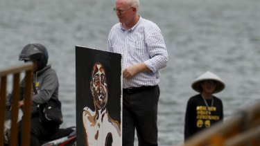 Lawyer Julian McMahon carries a self-portrait painted by Myuran Sukumaran, after visiting the prison island of Nusakambangan.