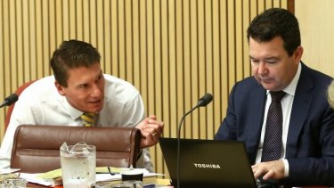Coalition senators Cory Bernardi and Dean Smith in discussion during estimates hearings in 2014.