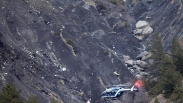 A rescue helicopter flies over debris of the Germanwings passenger jet.