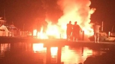 Locals watch on as the boats go up in flames.