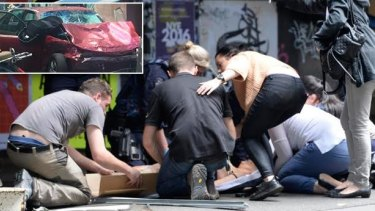 People help the injured after a car ploughed through pedestrians in Bourke Street.