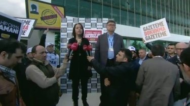 Sevgi Akarcesme (left), editor of <i>Today's Zaman</i>, addresses a rally after the government takeover of the newspaper.
