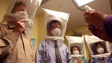 Medical staff test the seal of N95 respiratory masks.