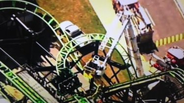Firefighters use a cherry picker to rescue people stranded on the Green Lantern ride at Movie World.