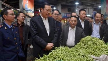 Panzhihua mayor Li Jianqin (third from left) and colleagues including gunman Chen Zhongshu (second from right) at a market just before Chinese new year.
