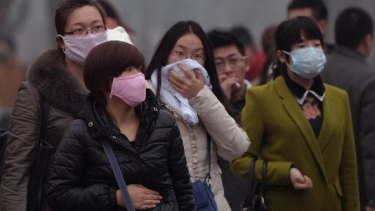 Chinese commuters wear face masks as heavy air pollution shrouds Beijing in February 2014. China's cities are often hit by heavy pollution, blamed on coal-burning by power stations and industry, as well as vehicle use.