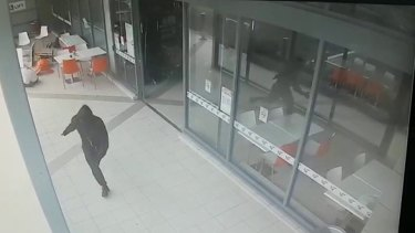 A hooded figure runs from Bankstown Central after shooting Wally Ahmad on April 29, 2016.
