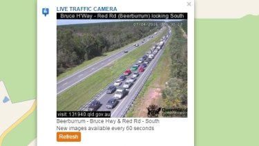 A car on fire on the Bruce Highway at Glasshouse Mountains is causing long delays. This traffic camera is at Red Road, about three kilometres south of the fire.