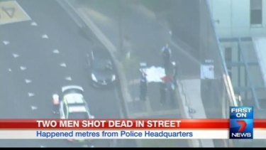 A sheet covers two bodies on the footpath outside police headquarters.