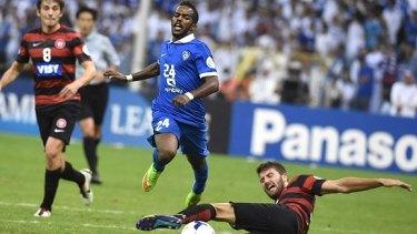 Antony Golec makes a tackle on Nawaf Al Abed (L).