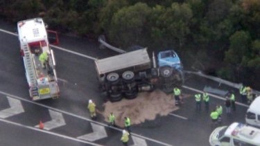 The clean-up begins after a truck rollover on the Mt Lindesay Highway, south of Brisbane.