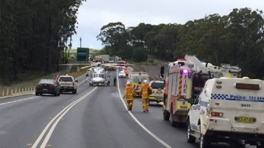 Police and emergency services at the scene of the fatal crash on the Princes Highway.