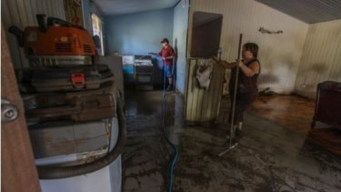 Marie Turner-Gomez helps with the clean up at Russell Keys flood-devastated home on Brisbane Terrace, Goodna.