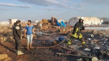 The aftermath of a reported air strike on a refugee camp in Syria.