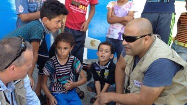Mohammed Al Halabi, right, is seen talking to children in his work as Gaza program manager for World Vision.
