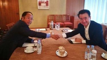 Huang Xiangmo, chairman of Yuhu Group, and entrepreneur Wang Jianlin of the Wanda group shake over the billion dollar deal.
