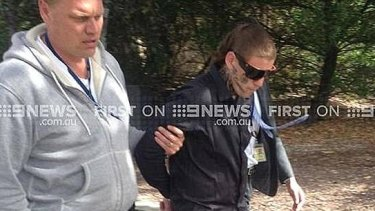 """Bradley Azzopardi is brought into court in Geelong last year, the words """"No Comment"""" tattooed on his face."""