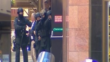 A screenshot from Channel Seven of tactical police as hostages leave the Lindt cafe.