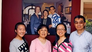 The Wang family in their Altona home, in front of a photograph of Julia Gillard and Jian and Zheng Wang.