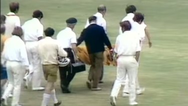 Ewen Chatfield is taken from the field after being struck by a bouncer from Peter Lever.