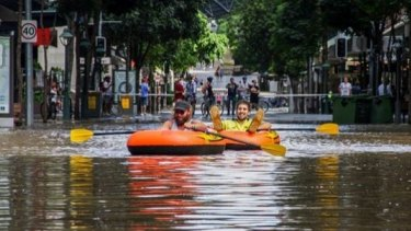 Keiran Beaumont and Sonny Grebe from Redcliffe, paddle their way through the Brisbane CBD.
