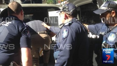 Police detain Mr Di Iorio after over the alleged flag burning.