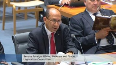 Senator Brandis reads poetry while Department of Foreign Affairs and Trade secretary Peter Varghese answers questions.