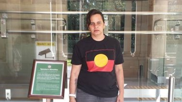 Janine Kelly was forced to cover up the Aboriginal flag on her T-shirt to enter Queensland's Parliament House on Tuesday.