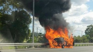 A car exploded in flames beside the Pacific Motorway on the Gold Coast on Wednesday morning.