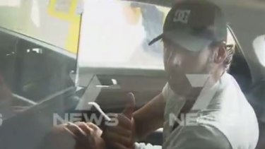 Grant Hackett is driven away by police from his parents' Gold Coast home.