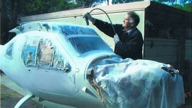 Robin works on his plane in the backyard.