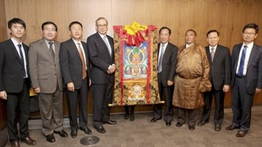 "Bob Carr with Chinese official Zhu Weiqun (also standing next to the scroll) and ""living buddha"" Tudeng Kezhu (wearing a robe)."