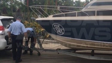 Police examine the boat that the five men towed from Melbourne to Cairns.