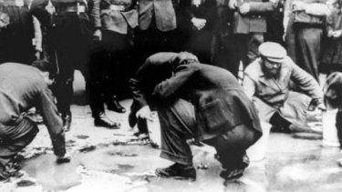 Jews in Vienna forced to scrub Schuschnigg's slogans off the sidewalk as Nazi soldiers watch.
