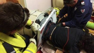 Rescue crews work to extricate the man trapped in the washing machine.