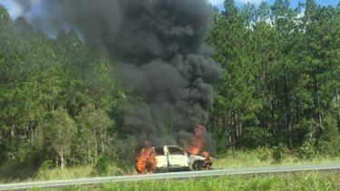 A car on fire on the Bruce Highway at Glasshouse Mountains.