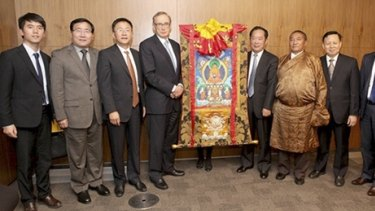 "Bob Carr with Zhu Weiqun (also standing next to the scroll) and ""living buddha"" Tudeng Kezhu (in robe) in a photo which appeared in the People's Daily, the Communist Party's flagship newspaper."