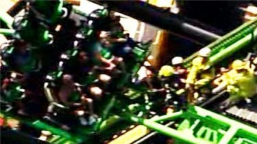 Emergency service staff work to free six people  stranded on the Green Lantern ride at Movie World.