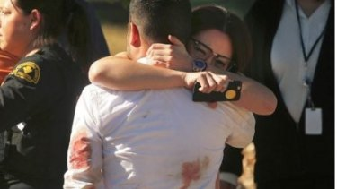 Survivors console each other at scene of the mass shooting in San Bernadino.