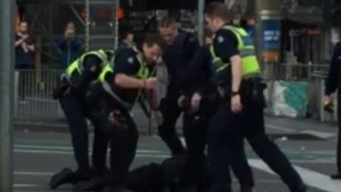 Police subdue the suspect at Flinders Street on Grand Final Day