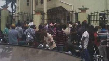 People gather outside the Catholic church in Ozubulu, Nigeria, after the fatal shootings.