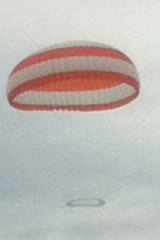 The stricken aircraft floats to earth under its parachute.