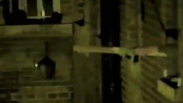 A drone outside the window of Wandsworth Prison as a man extends a stick to pull it closer.